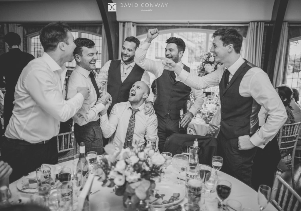A reportage candid shot of Groomsmen playing games during the wedding breakfast at Colshaw Hall in Cheshire