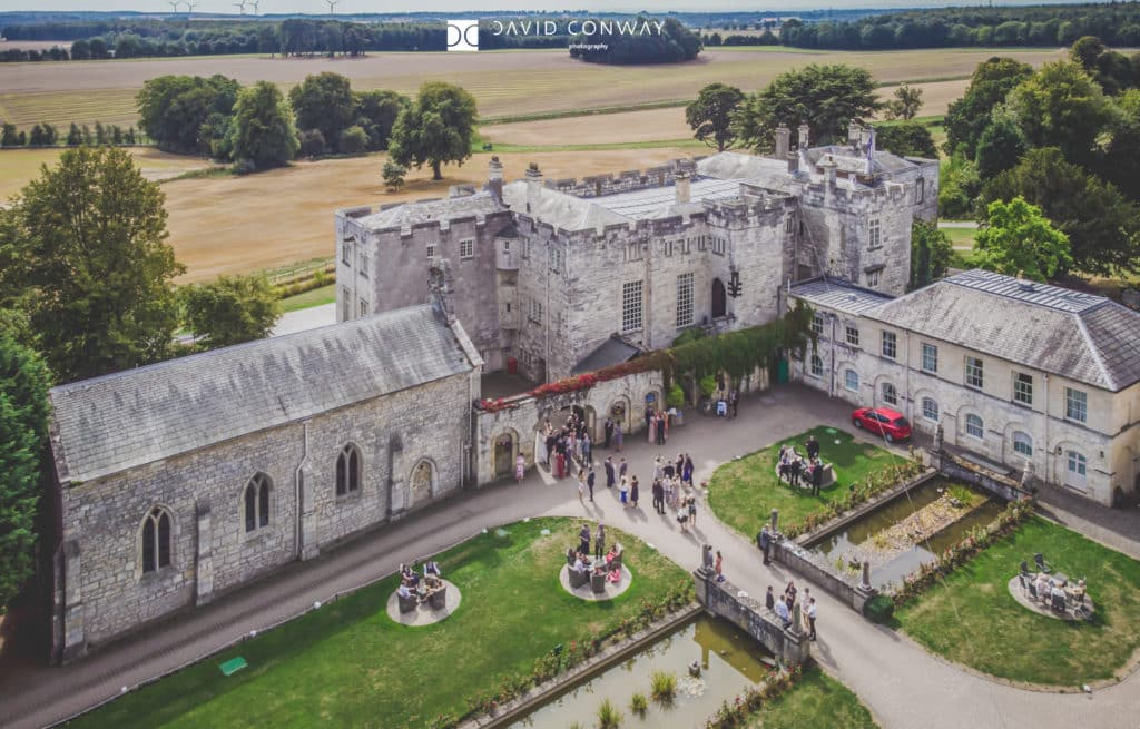 Drone shot of courtyard area whilst people have their drinks reception at Hazlewood Castle