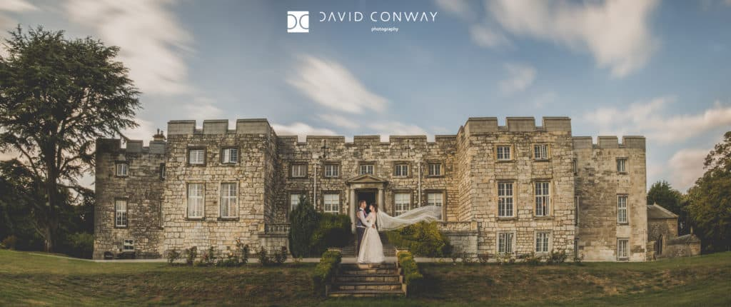 Bride and groom with floating veil outside the Castle at Hazlewood Castle wedding venue near York in West Yorkshire