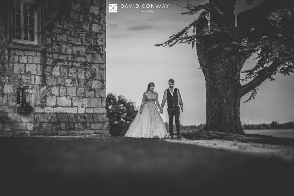 Black and white shot of Bride and groom walking outside Hazlewood Castle near York in West Yorkshire