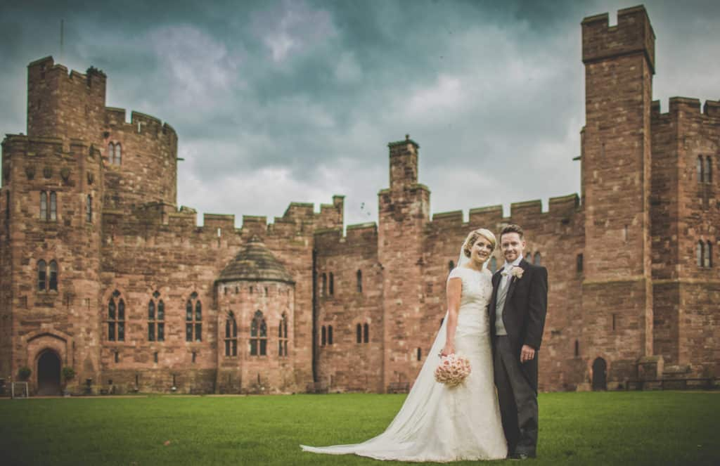 Bride and groom standing in front of Peckforton Castle