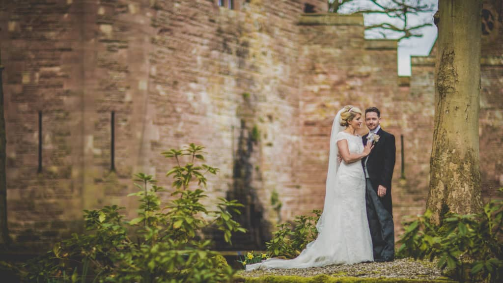 Bride and Groom standing infant of Peckforton Castle in Cheshire