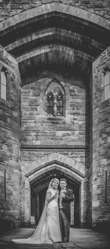Bride and groom stood in front of the gateway into Peckforton Castle in Cheshire