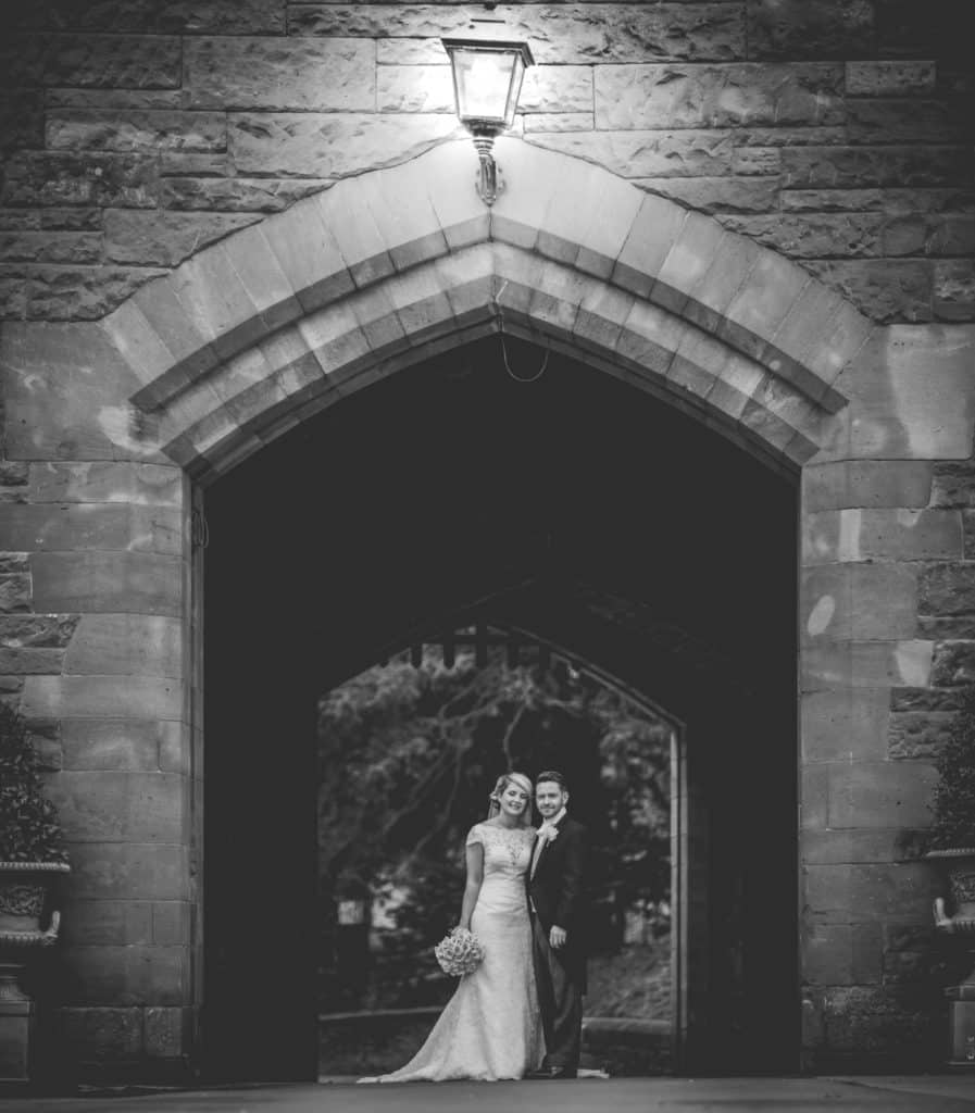 Bride and groom under an archway at peckforton castle in Cheshire