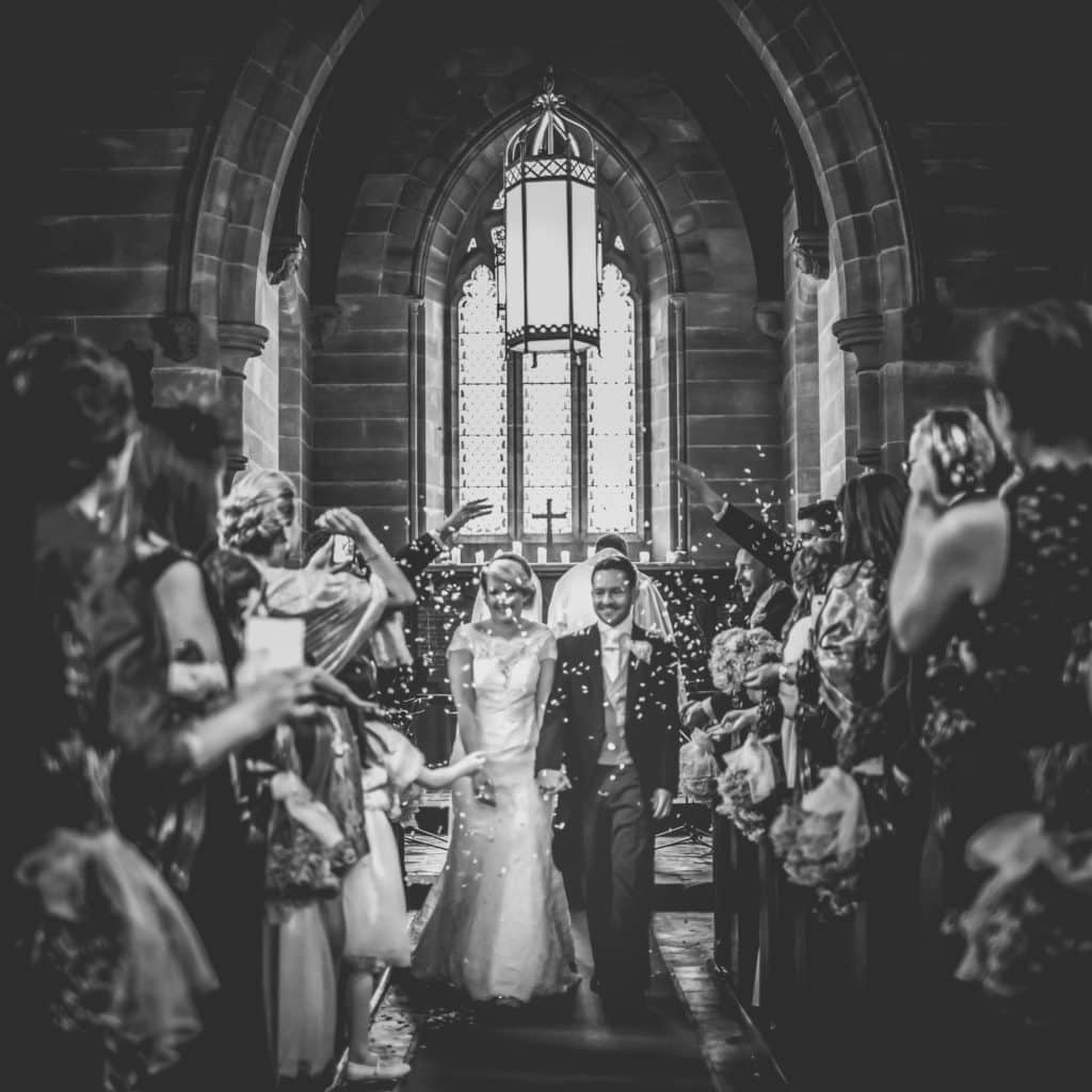 Bride and groom walking through the Chapel at Peckfortoin Castle whilst confetti is thrown