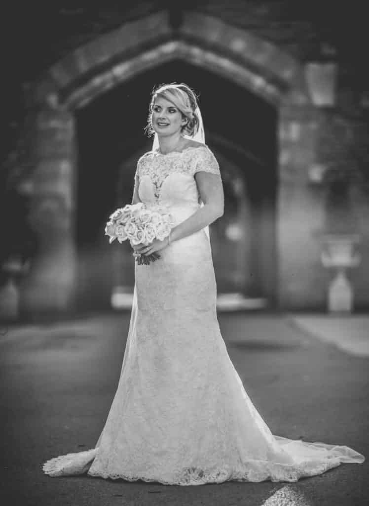 Bride in front of an archway at Peckforton Castle in Cheshire