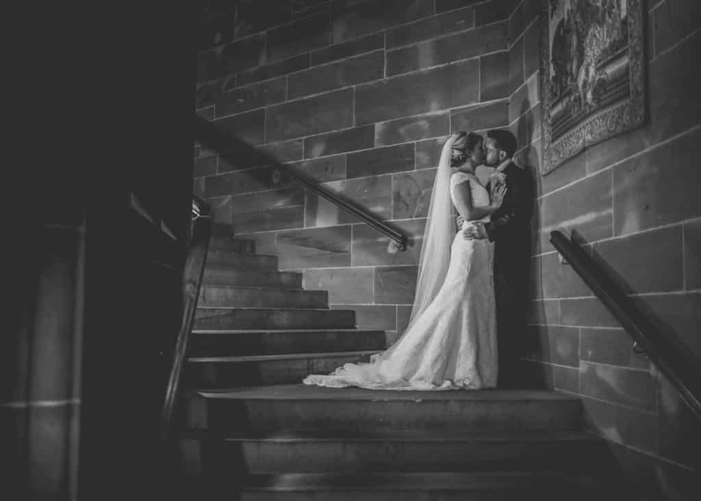 Bride and groom kiss on the stairs in Peckforton Castle in Cheshire