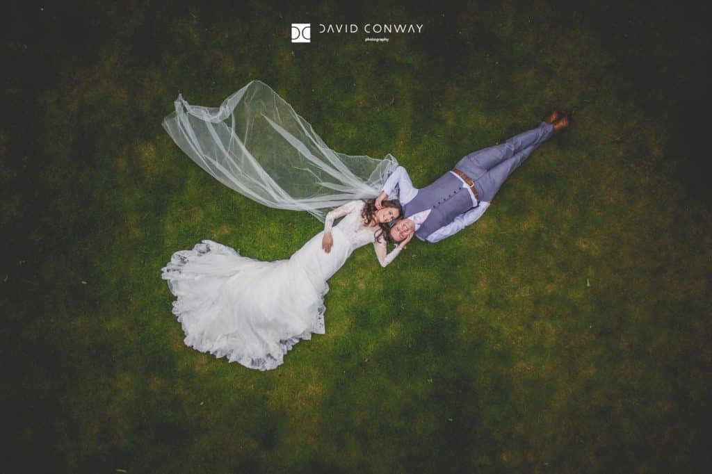 Arial shot of bride and groom lying on the grass