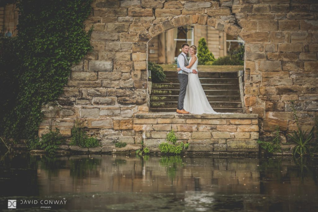 Bride and groom in the archway in front of the lake at Waterton Park Hotel in West Yorkshire