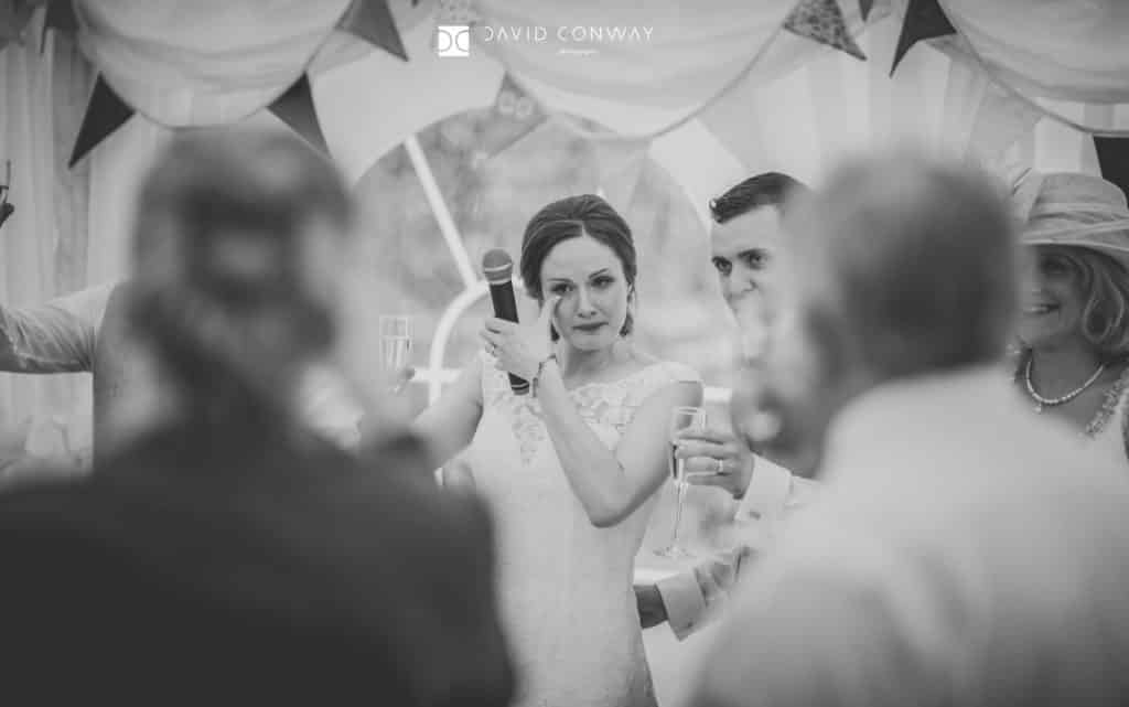 Bride wipes a tear from her eyes during as she cries during speeches at her wedding in Huddersfield, West Yorkshire