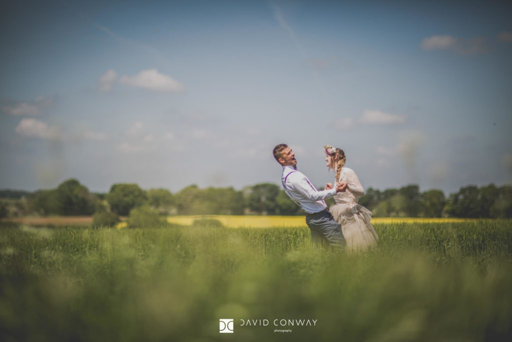 Bride and groom sharing a joke in a field surrounded by long grass in West Yorkshire