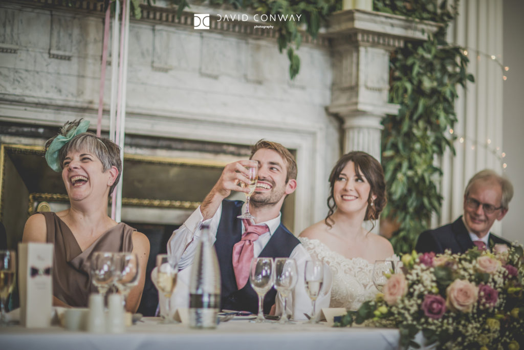 Bride and groom laughing during speeches in the great hall at Hazlewood Castle in West Yorkshire