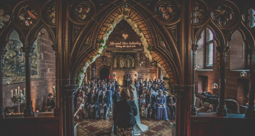 Bride and groom during their wedding ceremony in the great hall at Peckforton Castle