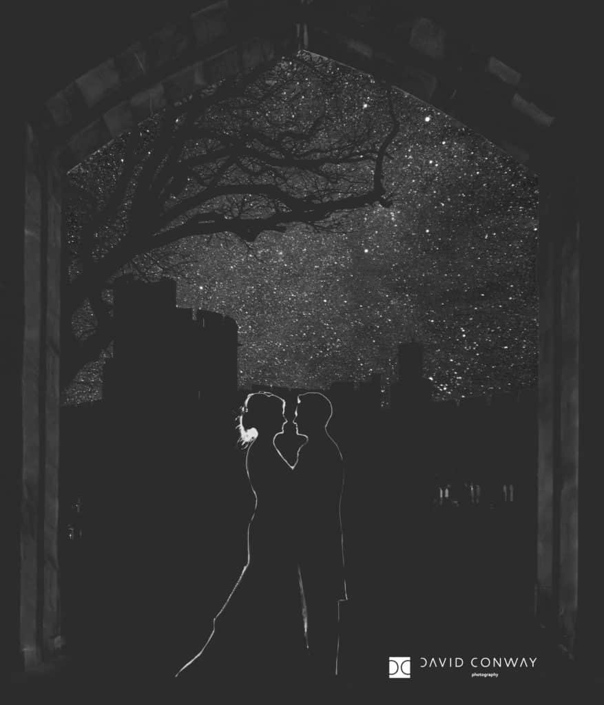 Bride and groom silhouette in an archway under the stars at Peckforton Castle