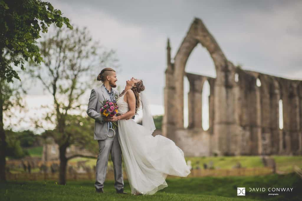 Bride and groom having a laugh together in front of Bolton Abbey's ruins.
