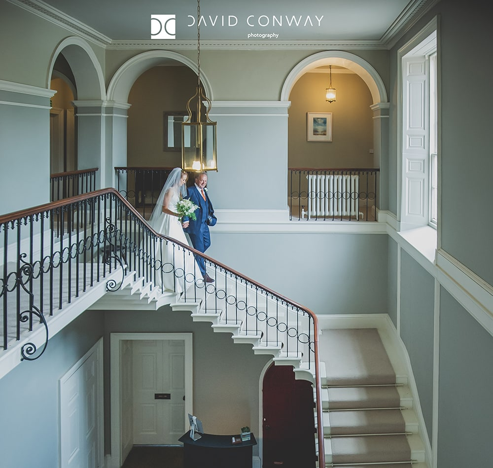 Bride-and-father-walking-down-stairs-at-Saltmarshe-hall