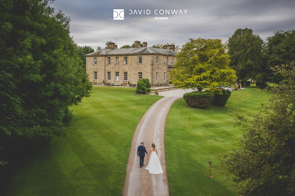 Drone-shot-of-bride-and-groom-walking-back-to-Saltmarshe-hall-by-west-yorkshire-photographer-david-conway