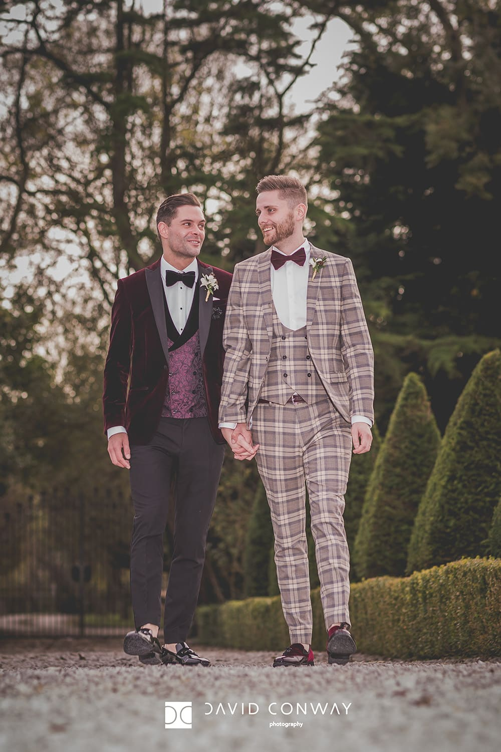 Groom-and-groom-hold-hands-and-take-a-romantic-walk-during-their-Wedding-Photographer-at-the-great-hall-at-mains-in-North-West-Same-Sex