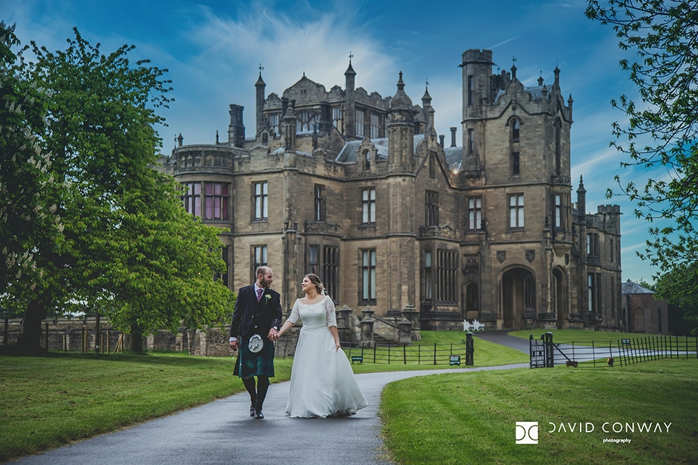Bride and groom walk hand in hand with Allerton Castle Wedding Venue behind them