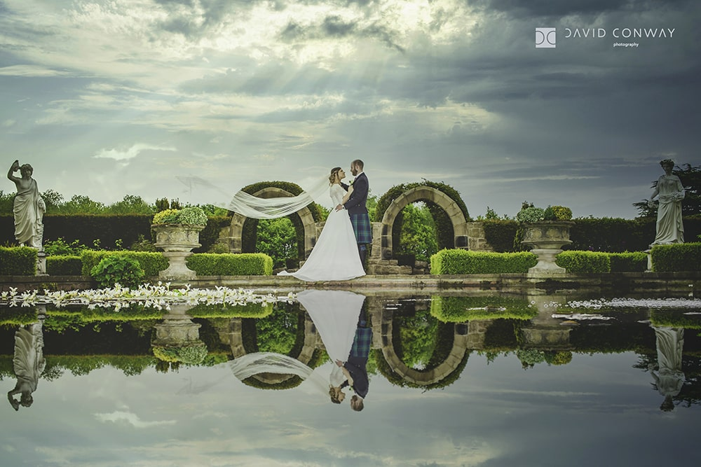 Bride and groom at Allerton Castle water feature