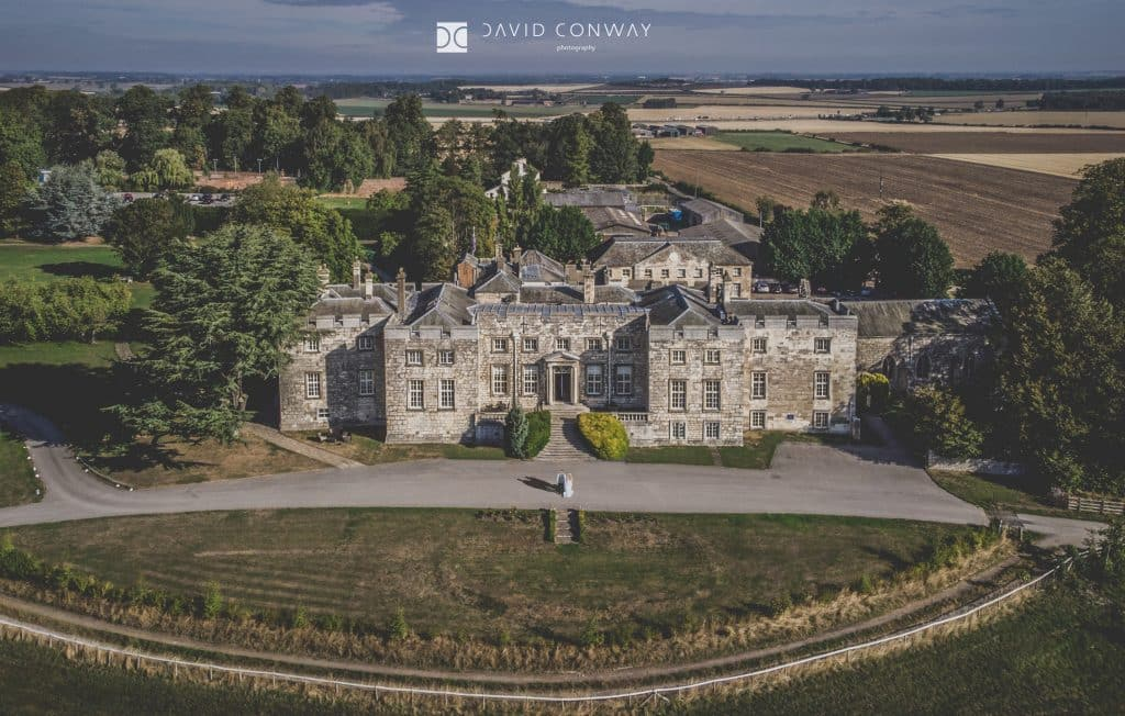 Bride and groom take a walk outside Hazlewood Castle drone shot