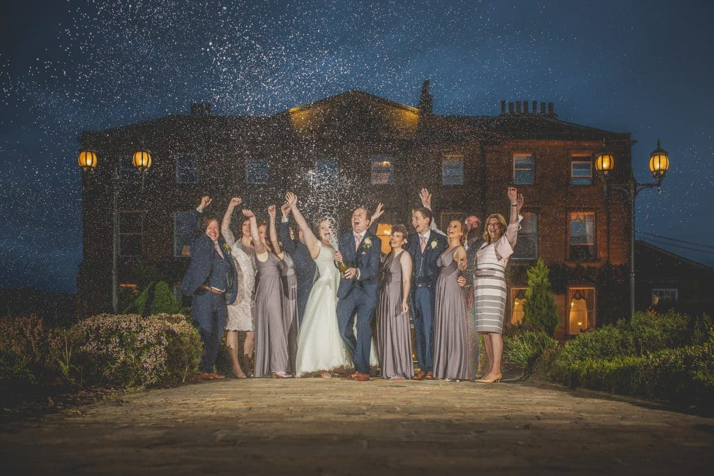 Bridal party with bride and groom spraying champagne