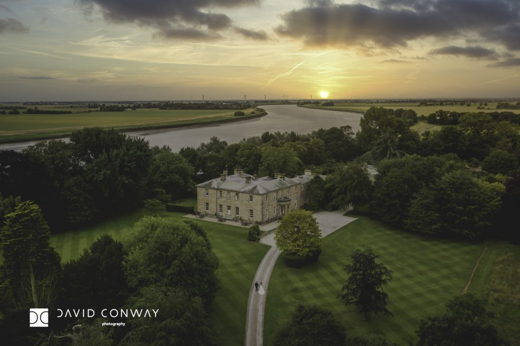 Drone shot of bride and groom at sunset walking towards Saltmarshe Hall by york wedding photography David Conway