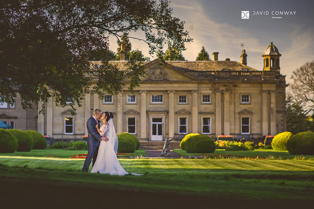 bride-and-groom-kissing-in-front-of-Wortley-Hall-wedding-venue-by-award-winning-wedding-photographer-davod-conway