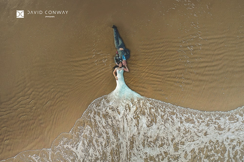 a-drone-shot-of-a-bride-and-groom-lying-on-the-beach-mermaid-by-west-yorkshire-wedding-photograper-david-conway
